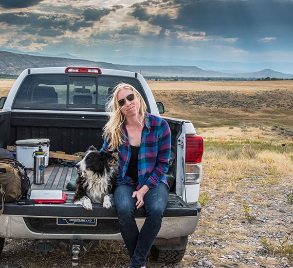 Alexis Bonogofsky sits on the back of her truck with her dog.
