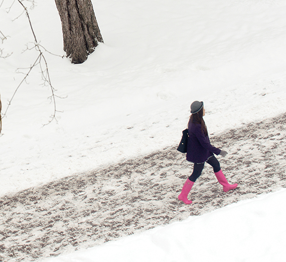 girl walking on snowy path marked by footprints