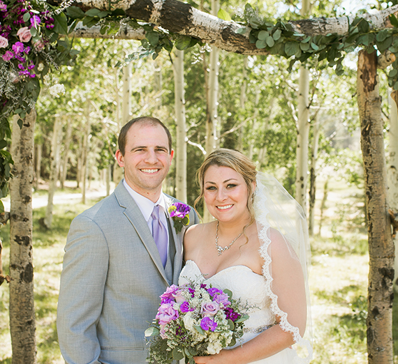 A man in a grey suit and purple tie stands under an outdoor wedding arch  next to his bride, who's wearing a wedding dress and holding a  bouquet.