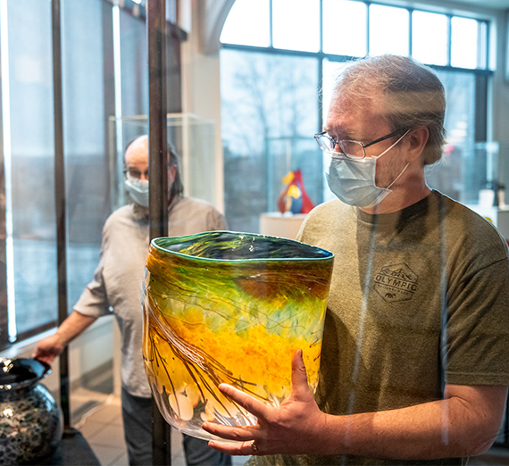 man handling a glass work by Dale Chihuly