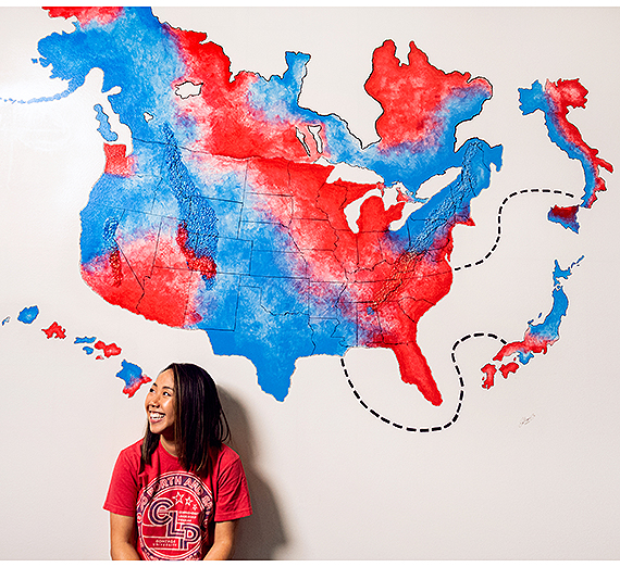 Cat Truong ('14) in front of the mural she created in Gonzaga's advancement office. (Photo by Zack Berlat)