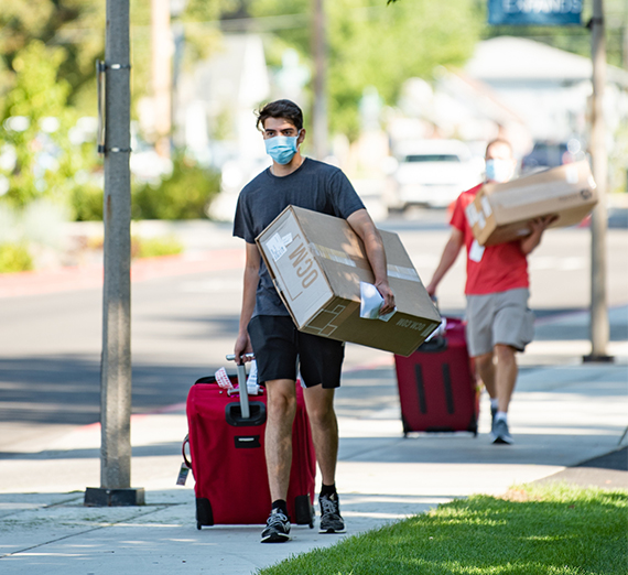 a student and family member haul items to a dorm
