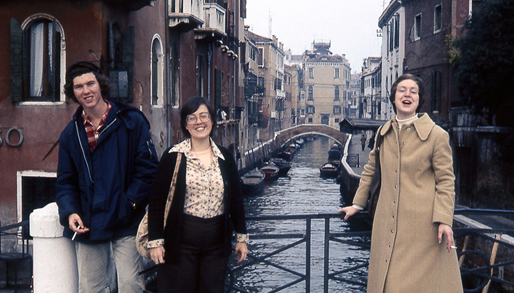 A group of three students smiling together on a bridge in Venice, Italy.