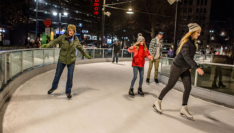Three people ice skate around a corner on the ice ribbon.