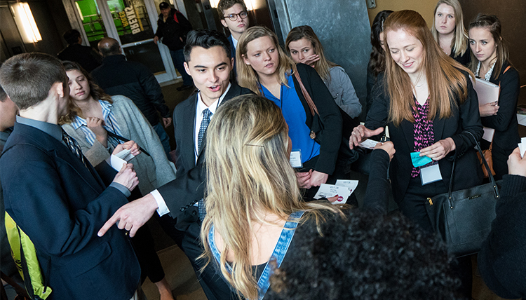 A group of students and professionals network and chat during a career trek.