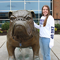 Emily Arnesen stands next to Spike the Bulldog.