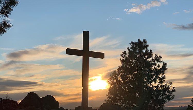 a cross backlit with the setting sun