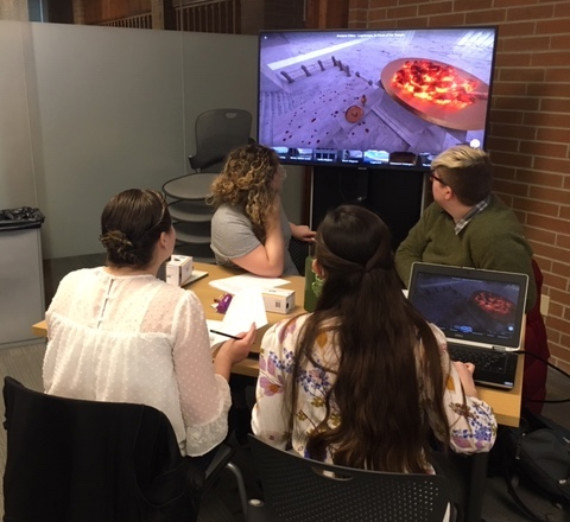 History students viewing an ancient site using a VR rendering.
