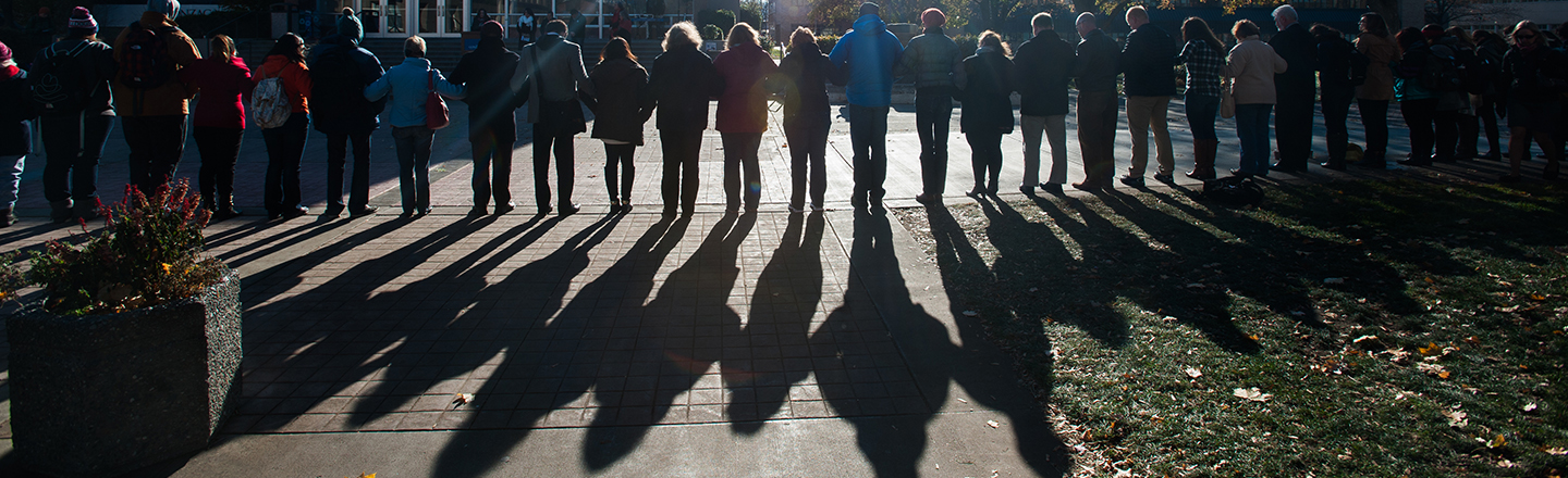group of people linking arms and shadow of the same