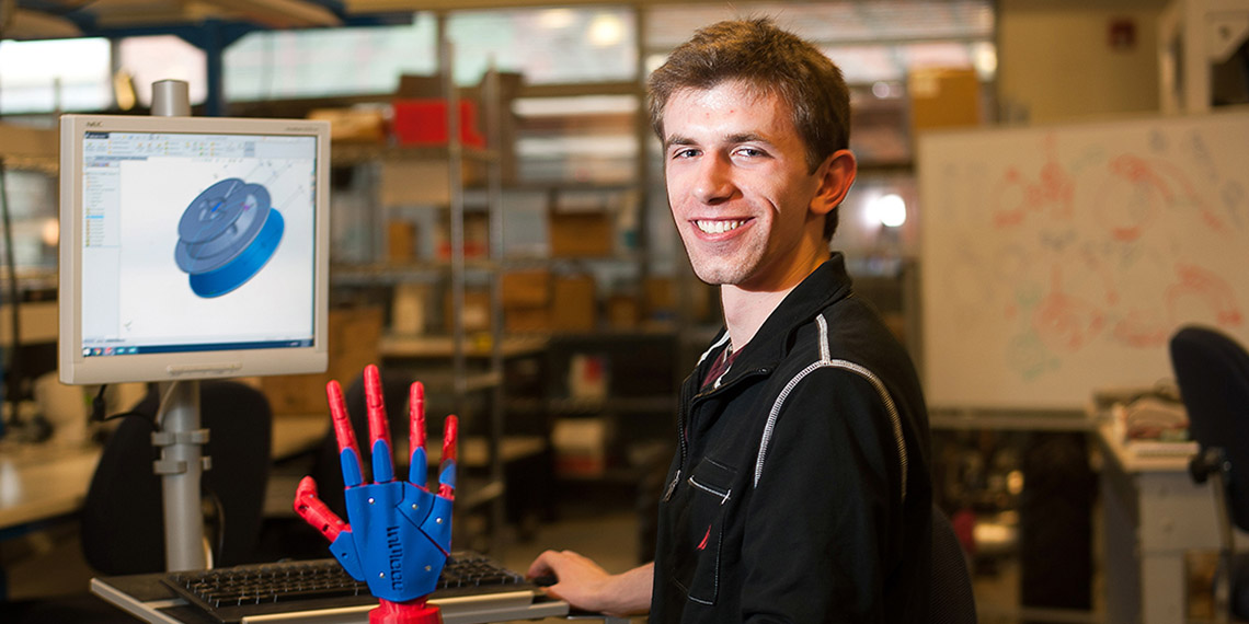 Gonzaga alum Christopher Birmingham in front of a computer screen, holding a robot hand he created