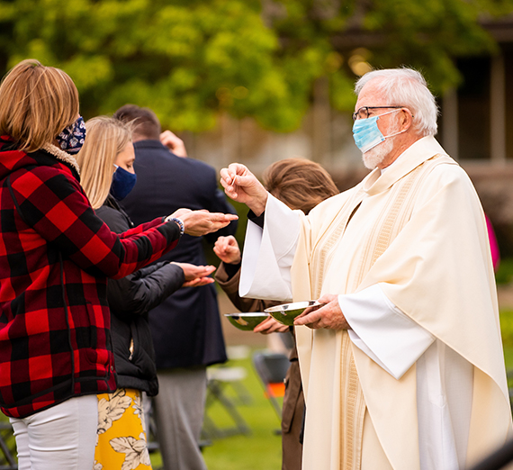 Priest offers communion at outdoor Mass