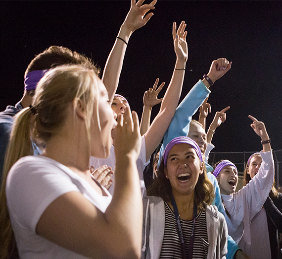 A group of students stands outside at night, cheering with arms raised.