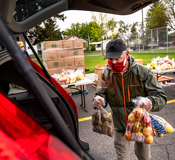 Volunteer loads food into vehicle.