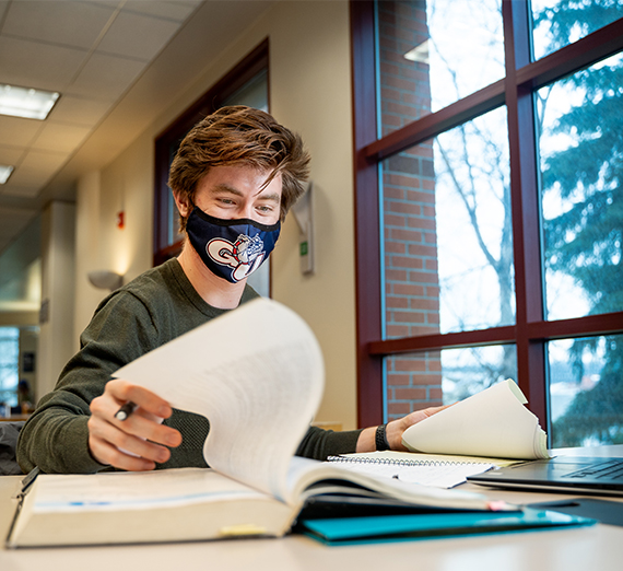 A student looks through a textbook and types on their computer while wearing a mask.