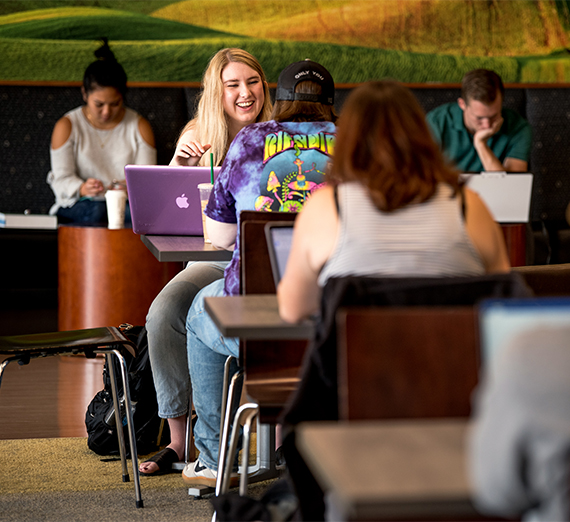 Students study at tables and benches in the Hemmingson student center.