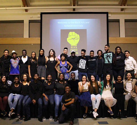 A group of students from the Black Student Union pose at an event.