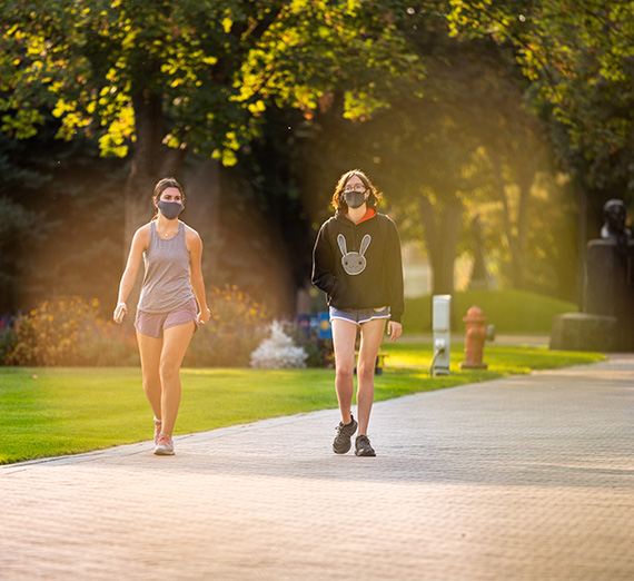 Two students wearing masks walk along a path on campus.