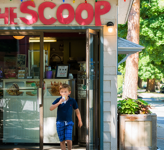 A young boy walks out of an ice cream shop licking an ice cream cone.