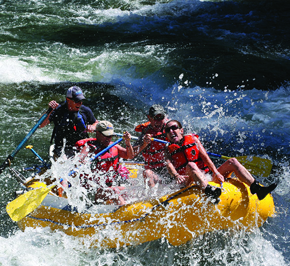 A group of students are hit with a wave as a guide navigates their raft through whitewater.