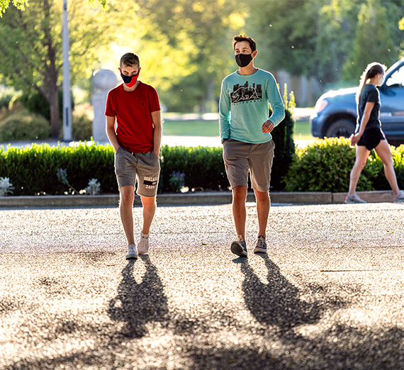 Two students walk through campus in the summertime while wearing masks.