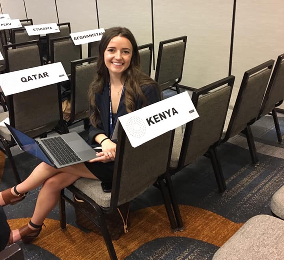 A student participating in Model UN sits next to a sign that says Kenya.