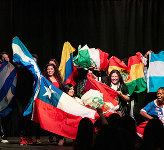 A group of students from La Raza holds up flags from Spanish-speaking countries.