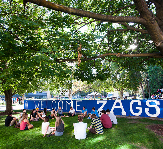 New students sit in a circle on the grass in front of a sign welcoming them to campus.