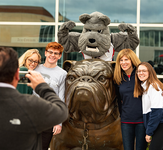 A man takes a photo of his family with a bulldog statue and Spike the bulldog mascot.