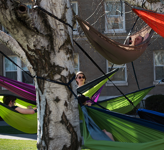 Students sit in hammocks hung between trees on campus on a beautiful sunny day.