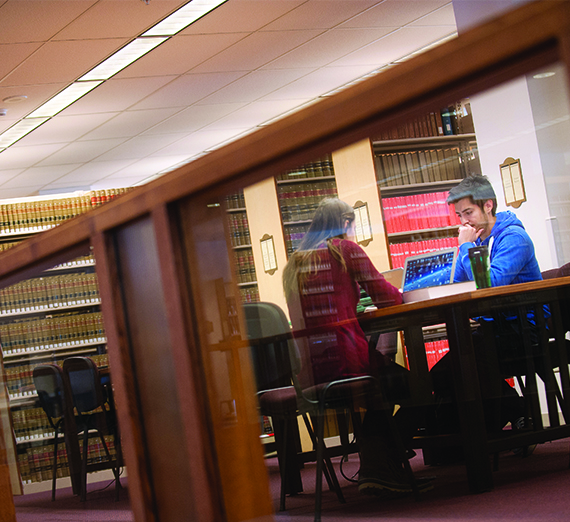 Two students sit and study at a table in the library.