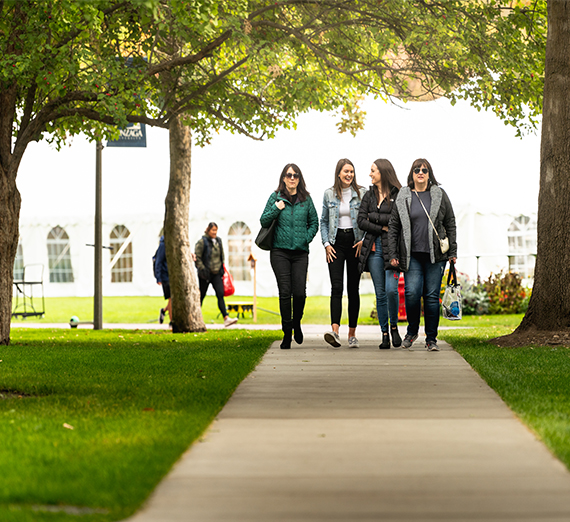 A group of visitors walk down a sidewalk while exploring campus.