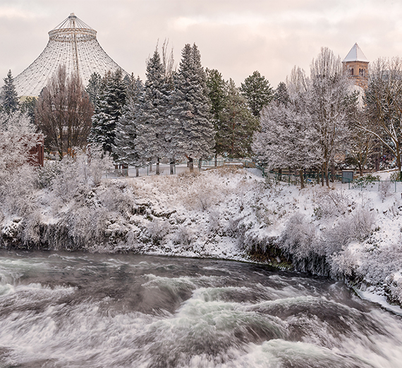 A snowy view of downtown Spokane, showing the river, pavilion, and clock tower in the park.