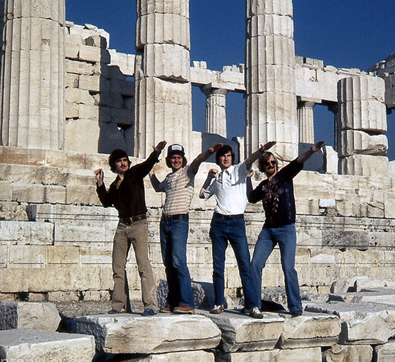 Four men - Joel DiGangi, Dan McLafferty, Tom Kearney, and Craig Sparrow - in Athens, Greece, posing at the base of the Parthenon in January 1976.