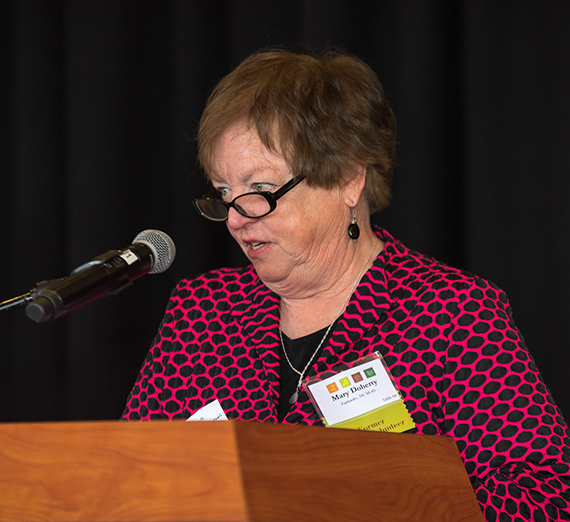 Woman with glasses and short, brown hair speaks at a podium in front of a black background.
