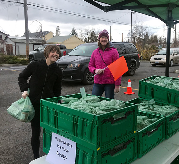 ZoNE Project Director Amber Waldref and volunteers work at a food distribution site in Northeast Spokane