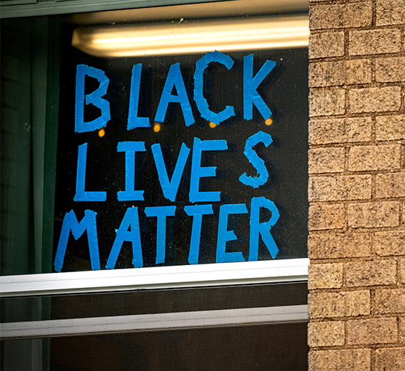 blue painters tape on a window reads black lives matter
