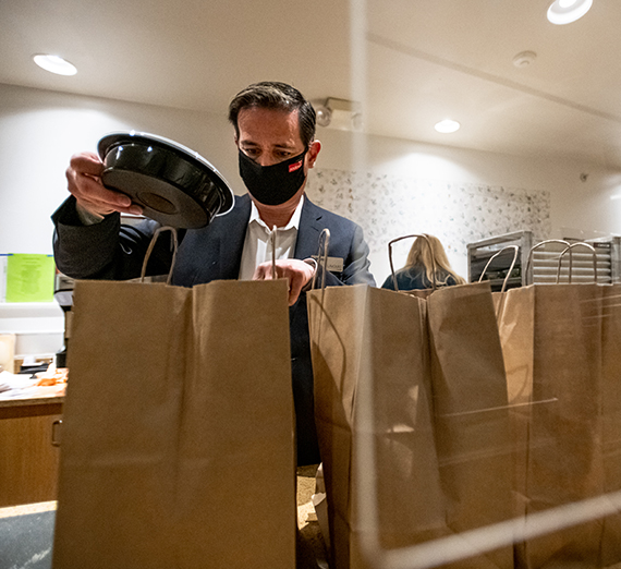Man putting food into a brown paper bag