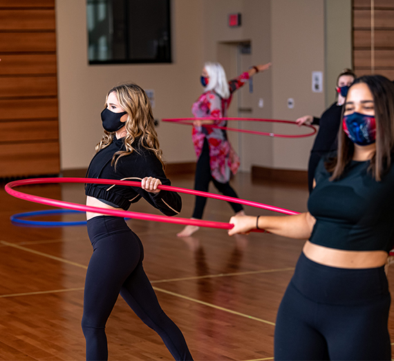 students dance with hula hoops to maintain distance