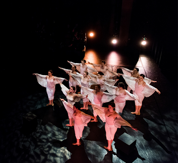 group of dancers on a dark stage