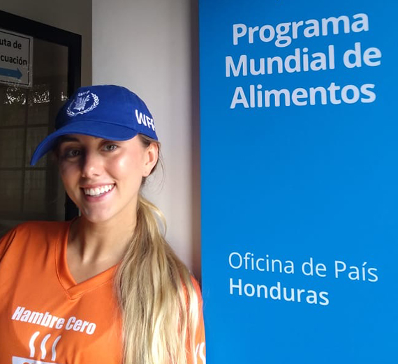"Erin Bergmann posing in front of sign that says ""World Food Program"" and ""Country Office of Honduras"""