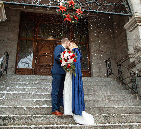 Two people kiss on church steps while snow falls.