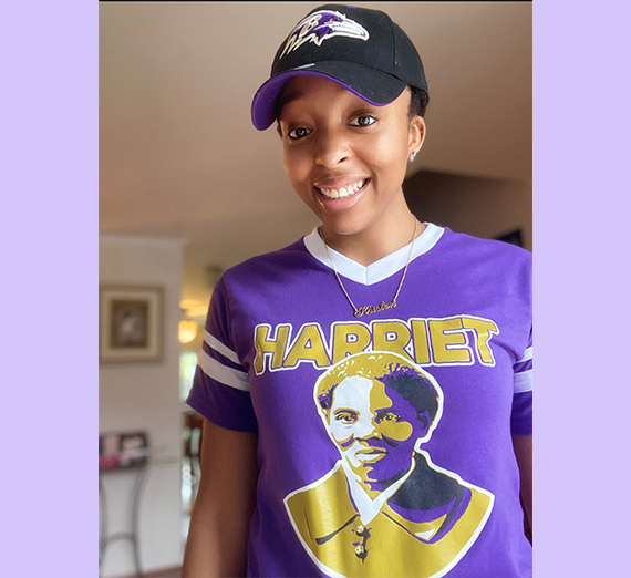 young black woman in purple shirt with photo of Harriet Tubman