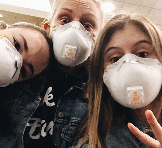 three people wearing protective masks
