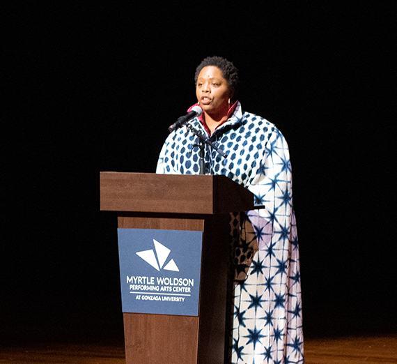 Woman speaking behind a podium onstage at the Myrtle Woldson Performing Arts Center