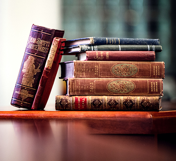 A stack of rare books, covers slightly worn and faded, piled on a table in Foley Library.