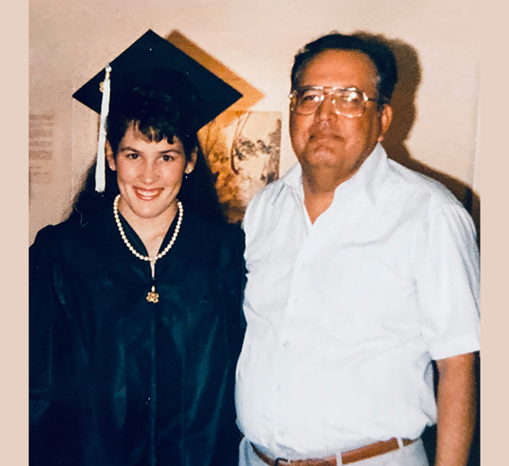 female college grad in cap and gown with father
