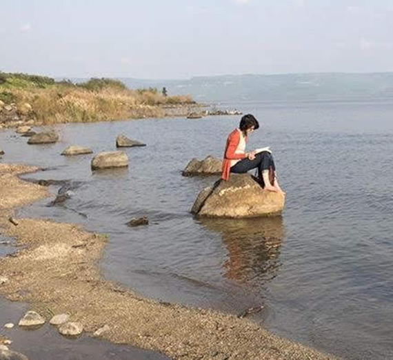 woman on rock at shore of sea of galilee