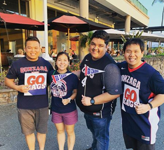 4 people hold go zags signs in hawaii