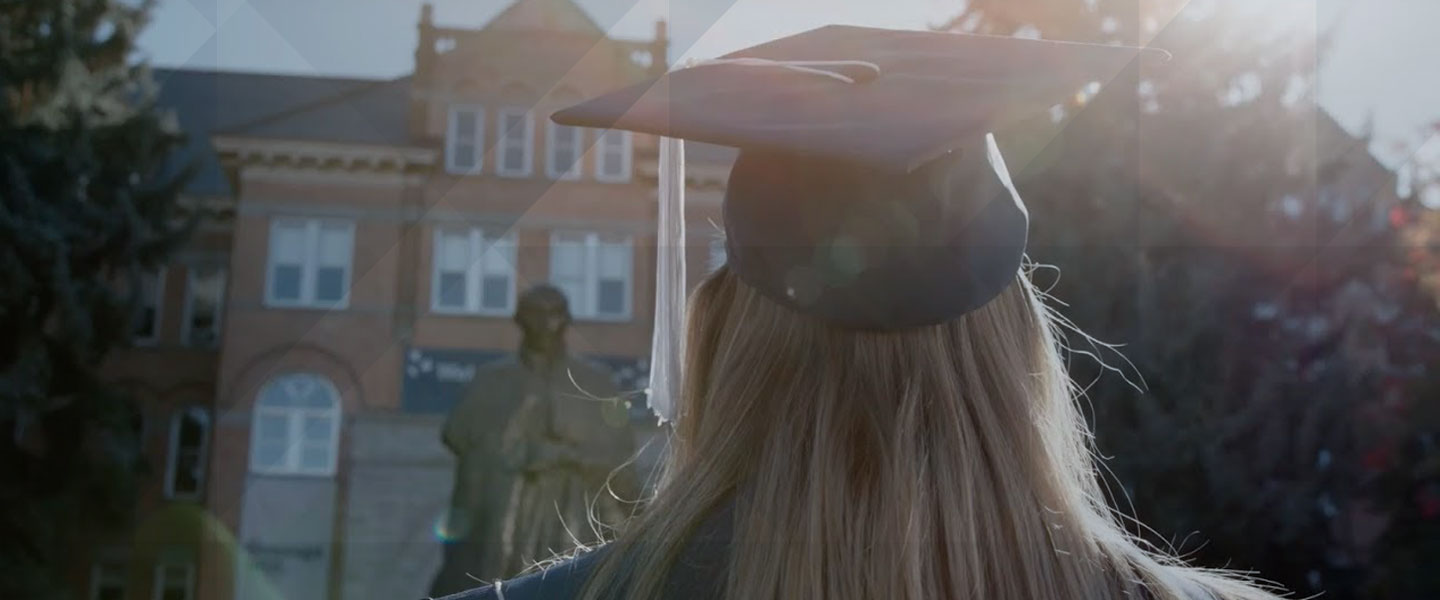 Stylized photo of female student in graduation cap and gown standing in front of St. Ignatius statue and College Hall on Gonzaga University campus