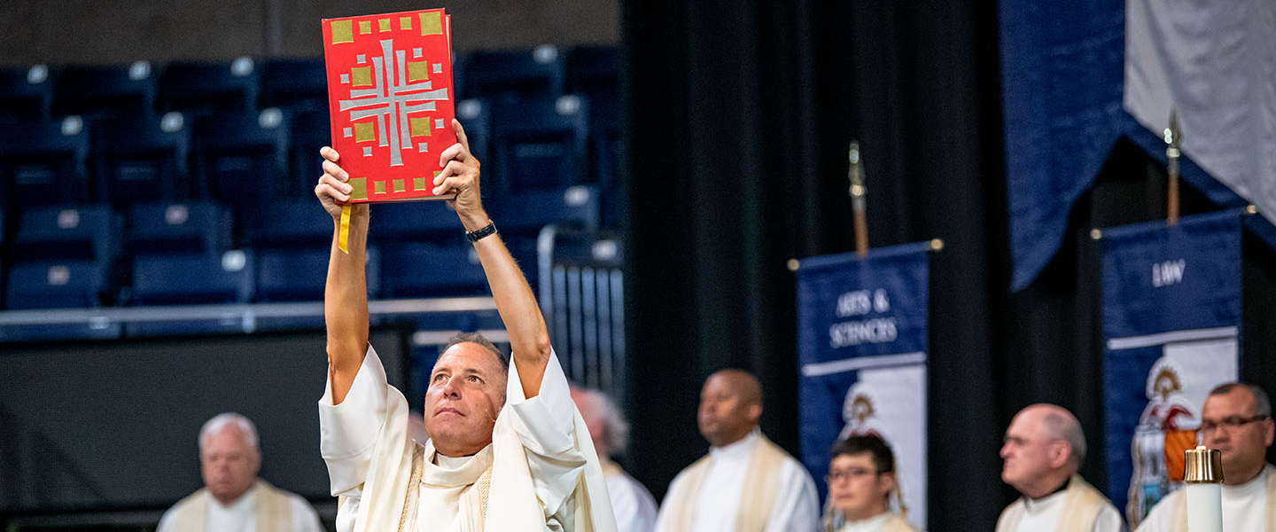 Fr. Hess holding up the book of the gospels at commencement mass